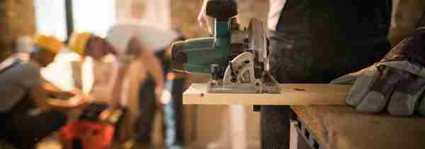 Carpenter using electric saw in workshop with workmen in background