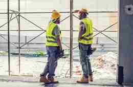 Tradesmen Talking And Leaning On Scaffolding